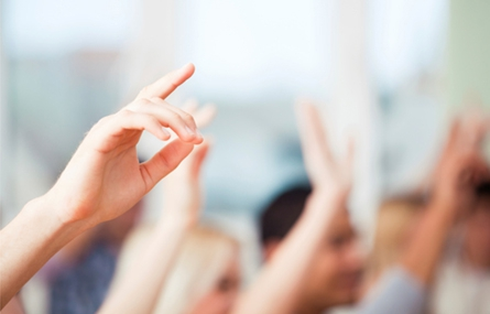 Photo of students raising their hands in a classroom